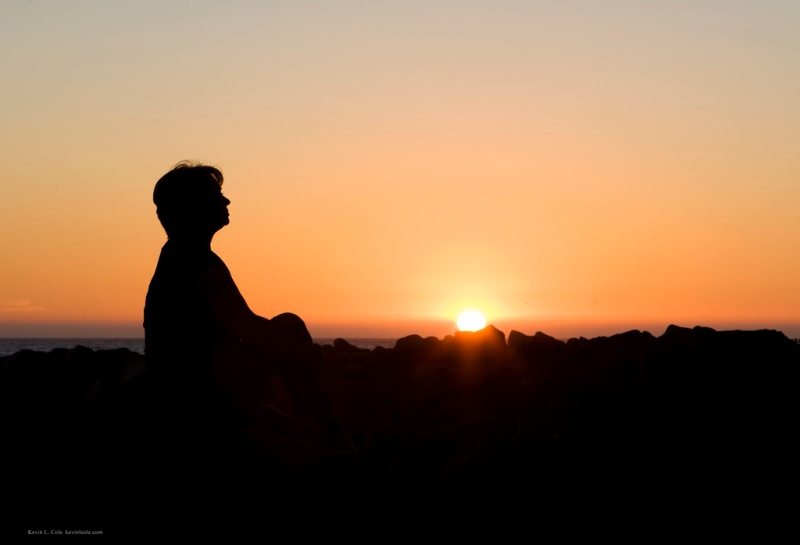 A silhouette of a woman sitting and watching the sunset