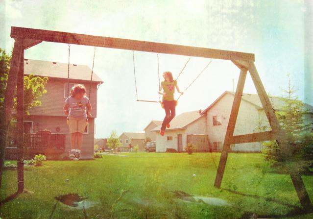 Sisters swinging on swingset in backyard